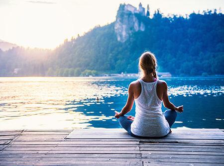 Frau im Meditationssitz mit Ausblick auf einen See