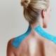 Frau mit Tape auf den Schultern - Taping