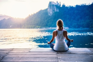 Frau meditiert am See - Yogalehrerausbildung