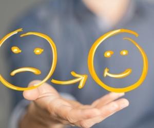 Psychologische Schmerztherapie - Therapeut hält Smileys